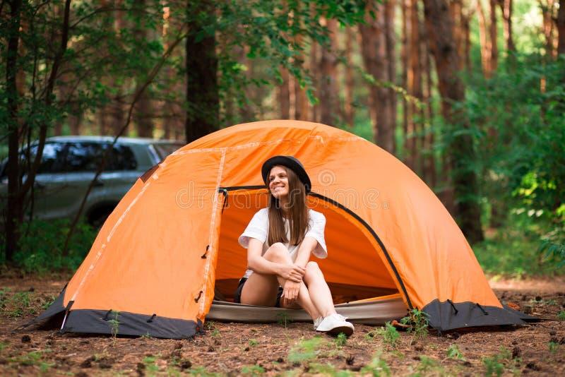 Giovane donna che riposa in cappello vicino alla tenda di campeggio in regione selvaggia immagine stock