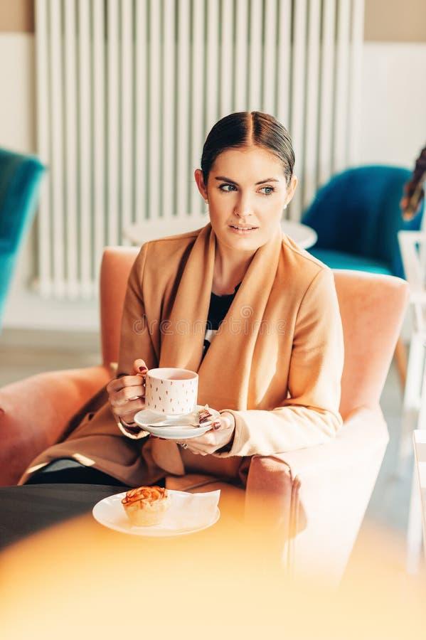 Giovane donna che riposa con la tazza di tè in caffetteria fotografia stock