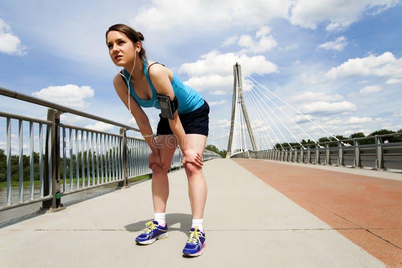 Giovane donna che riposa dopo il funzionamento in abiti sportivi blu sopra il brid immagini stock