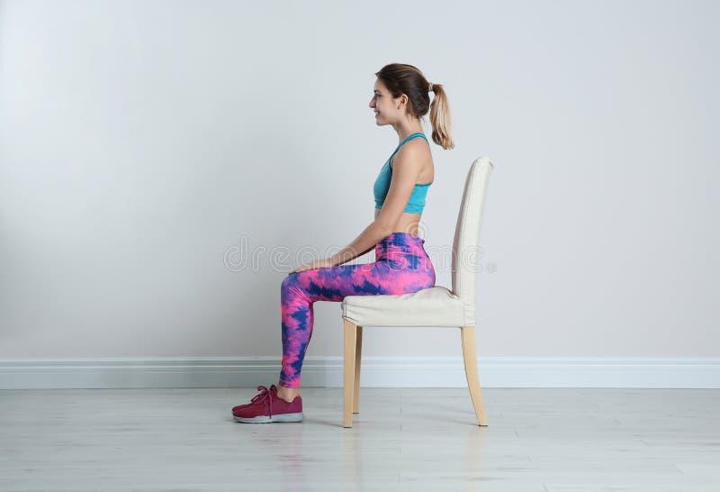 Giovane donna che riposa nella sedia dopo gli sport che si preparano vicino alla parete bianca fotografia stock