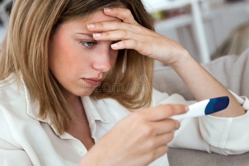 Giovane donna che ritiene deprimente e triste dopo l'esame del risultato del test di gravidanza a casa fotografie stock