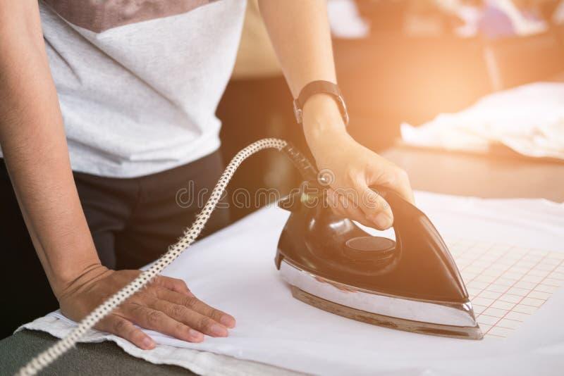 Giovane donna che riveste di ferro film impermeabile su tessuto al negozio lavoratore wo fotografia stock