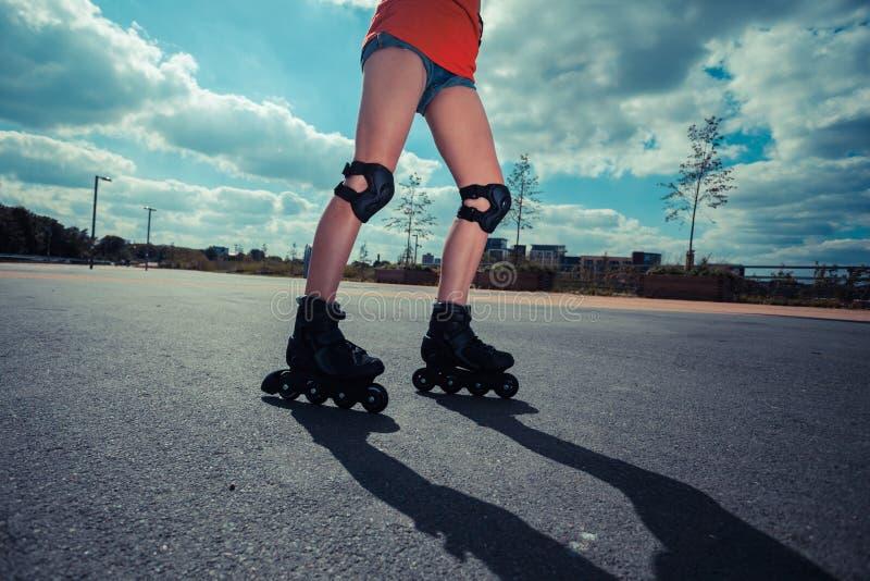 Giovane donna che rollerblading il giorno soleggiato fotografia stock
