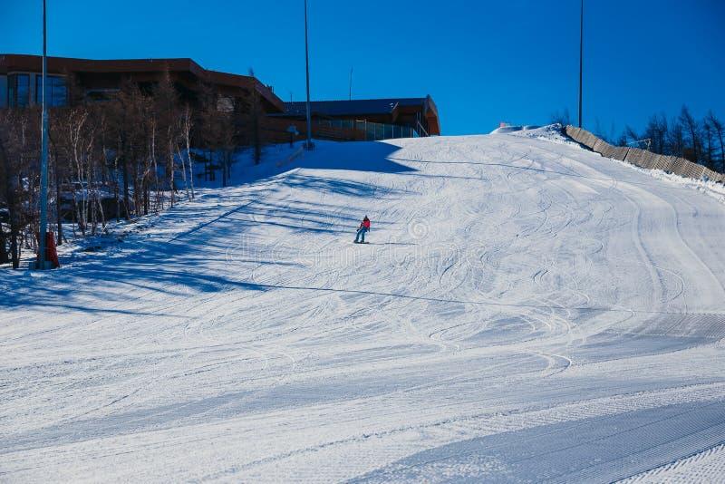 Giovane donna che rotola giù un pendio di montagna su uno snowboard fotografia stock libera da diritti