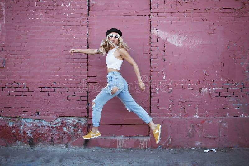 Giovane donna che salta al muro con occhiali da sole e cappello nero fotografia stock libera da diritti
