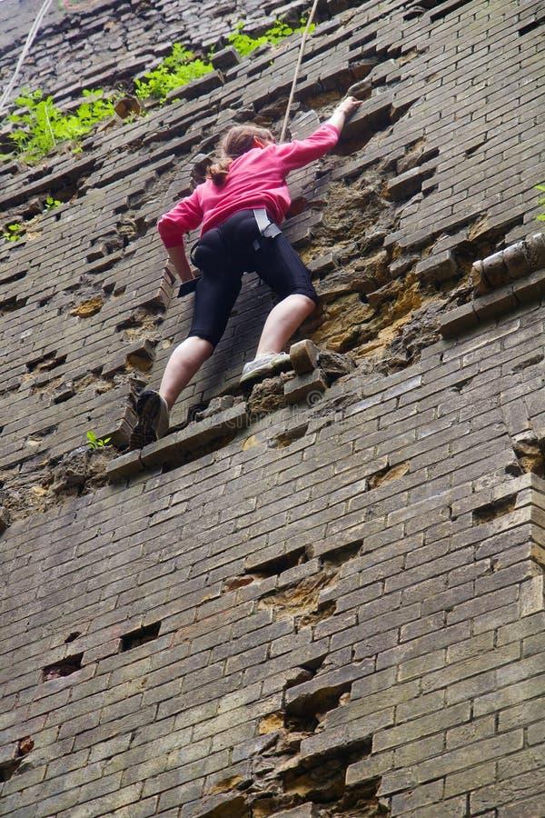 Giovane donna che scala muro di mattoni fotografie stock libere da diritti