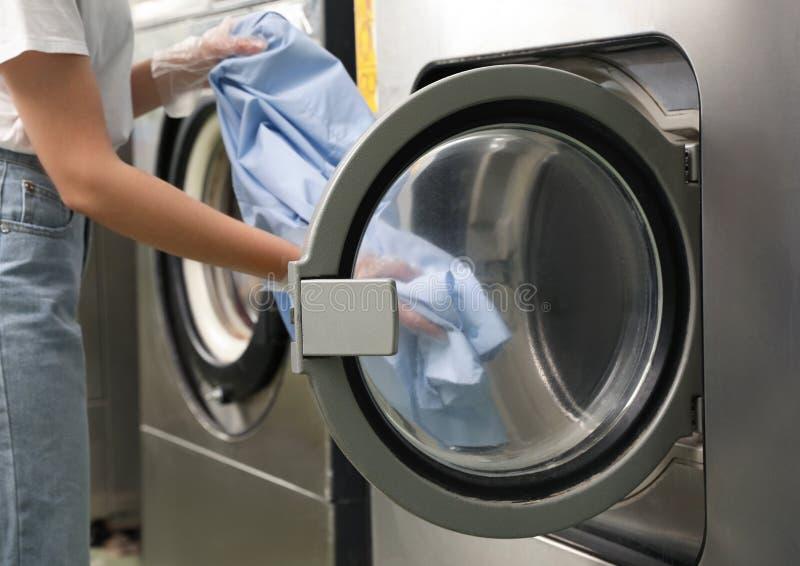 Giovane donna che scarica lavatrice nel lavaggio a secco fotografia stock