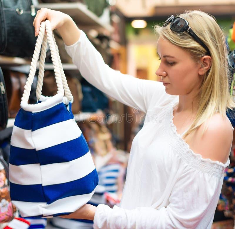 Giovane donna che sceglie la borsa della spiaggia immagini stock libere da diritti