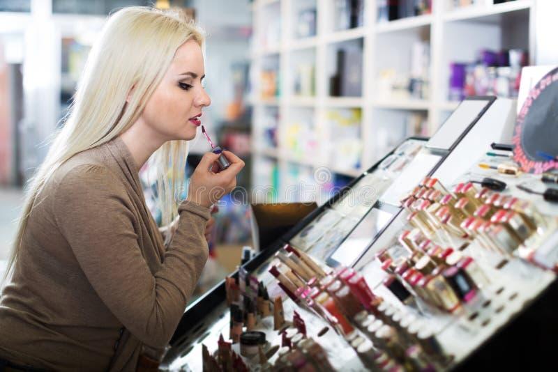 Giovane donna che sceglie labbro più grassoccio fotografie stock