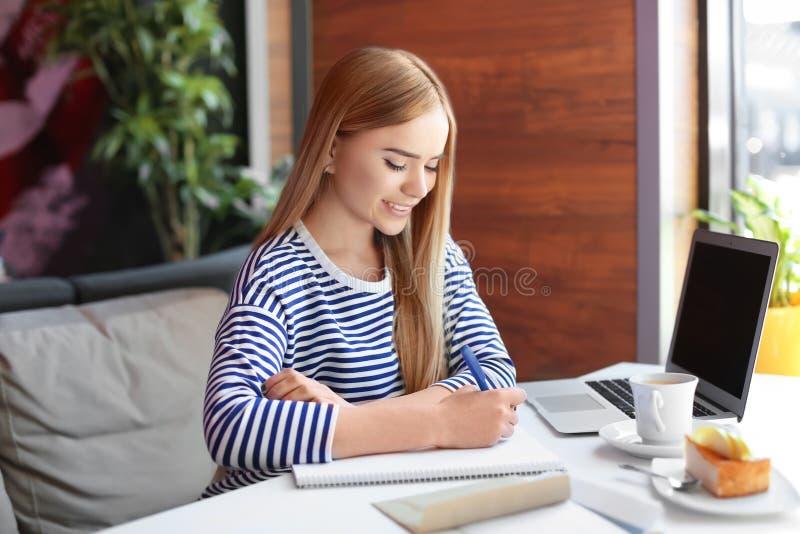 Giovane donna che scrive lettera alla tavola in caffè consegna di posta immagine stock libera da diritti