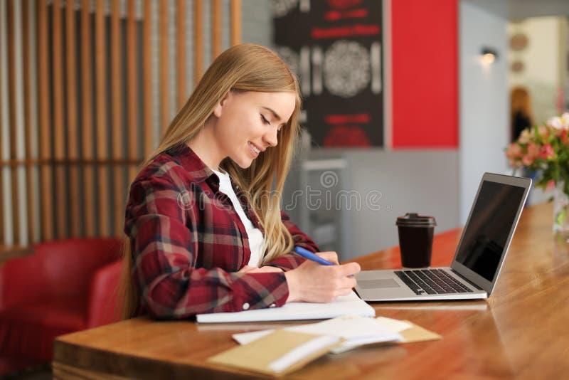 Giovane donna che scrive lettera alla tavola in caffè consegna di posta fotografie stock