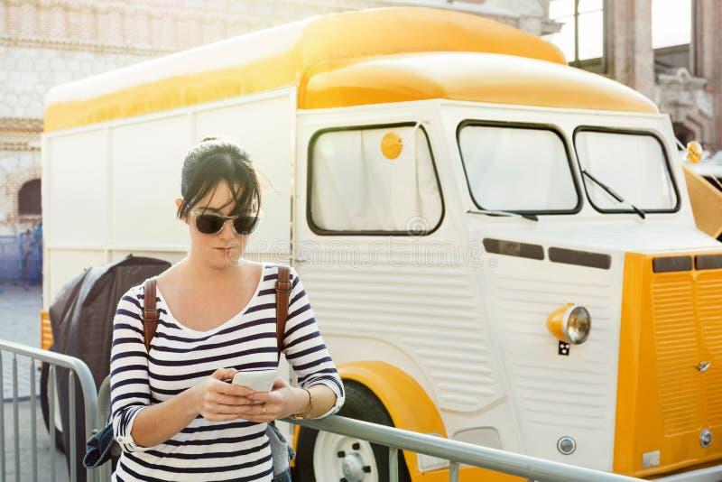 Giovane donna che scrive un messaggio sul suo cellulare, accanto al porcile d'annata fotografie stock