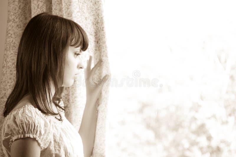 Giovane donna che sembra finestra esterna fotografia stock