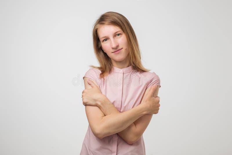 Giovane donna che si abbraccia che sorride e che sogna Colpo dello studio fotografia stock