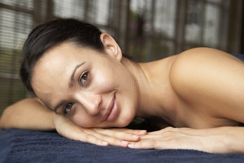 Giovane donna che si distende sulla Tabella di massaggio immagine stock