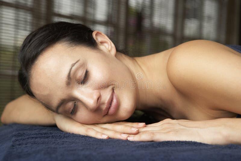 Giovane donna che si distende sulla Tabella di massaggio immagini stock