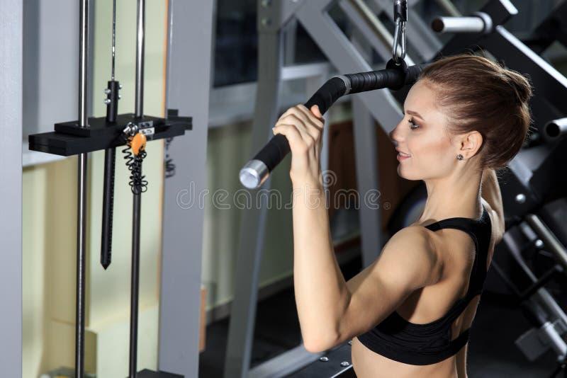 Giovane donna che si esercita indietro sulla macchina nella palestra e che flette i muscoli - modello atletico muscolare di forma fotografia stock libera da diritti