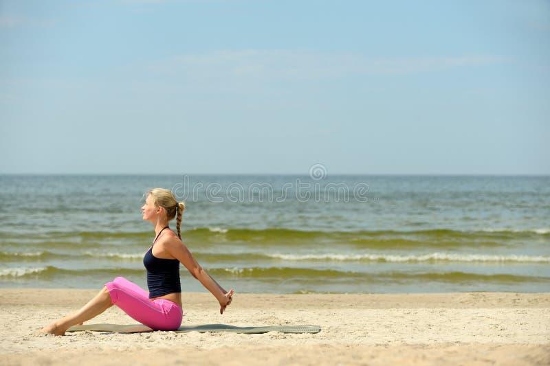 Giovane donna che si esercita sulla spiaggia fotografia stock libera da diritti