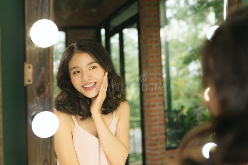 Giovane donna che si guarda riflessione in specchio a casa fotografia stock
