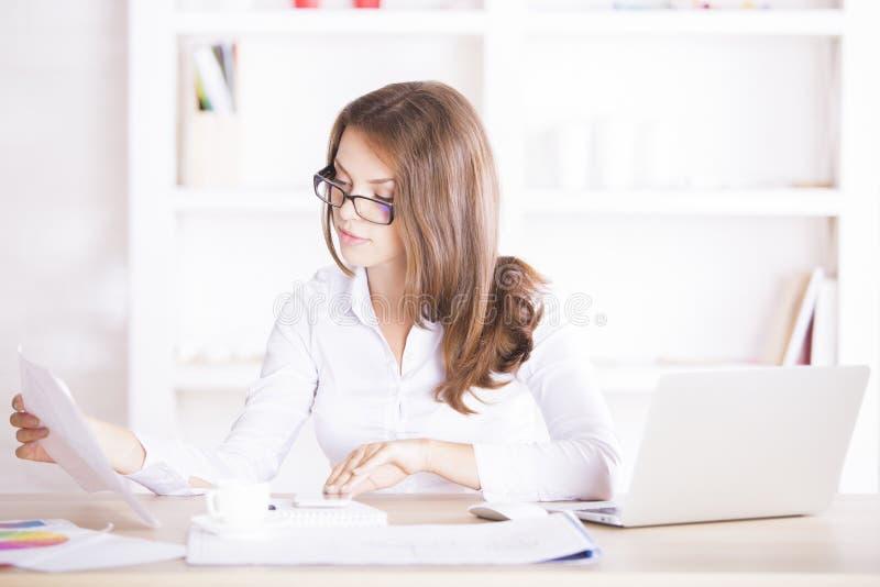 Giovane donna che si occupa del lavoro di ufficio fotografia stock