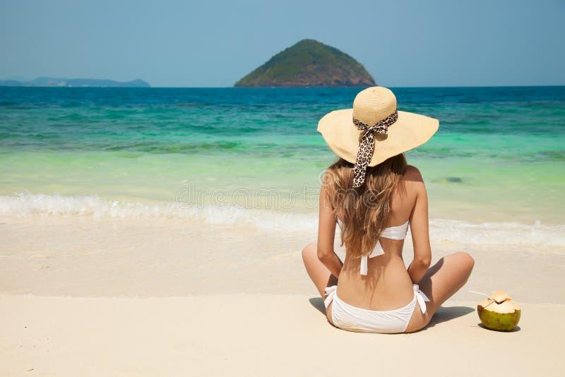 Giovane donna che si rilassa alla spiaggia tropicale fotografie stock libere da diritti
