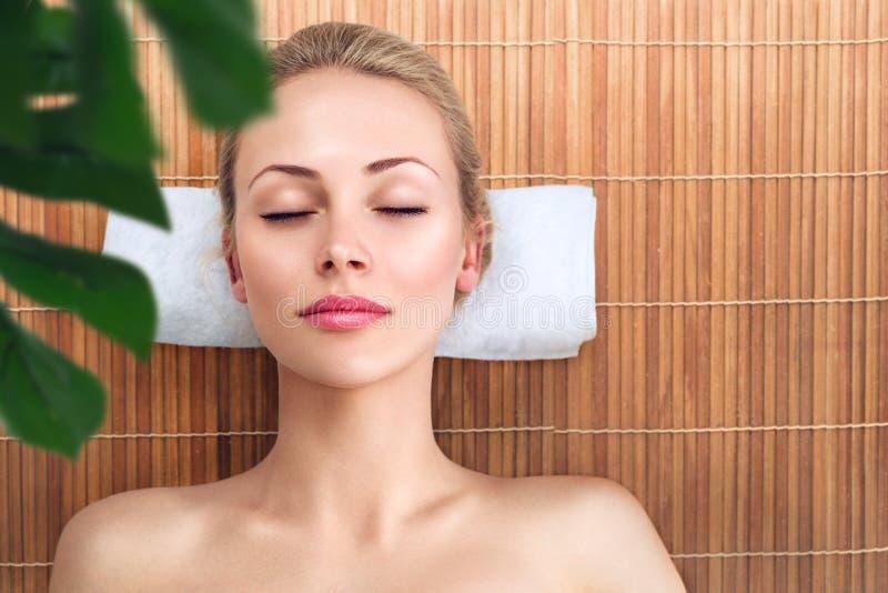 Giovane donna che si rilassa con il massaggio in stazione termale immagine stock libera da diritti