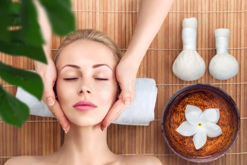 Giovane donna che si rilassa con il massaggio in stazione termale fotografie stock