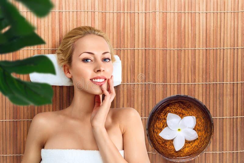 Giovane donna che si rilassa con il massaggio in stazione termale immagine stock