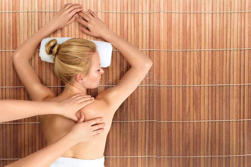 Giovane donna che si rilassa con il massaggio in stazione termale fotografia stock libera da diritti