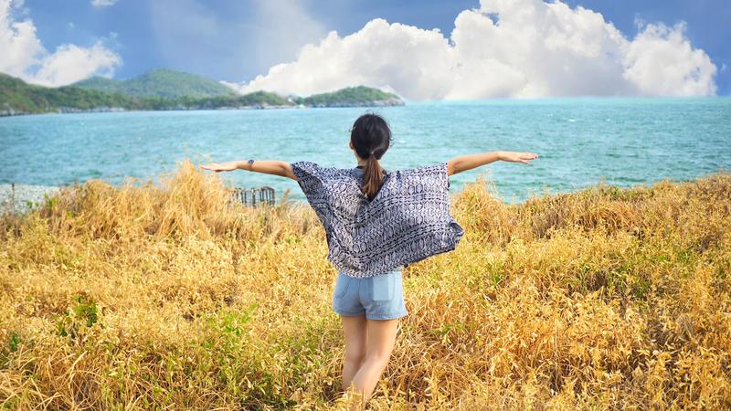 Giovane donna che si rilassa con il prato, il mare, la montagna, il cielo blu e la nuvola a Koh Sichang immagini stock libere da diritti