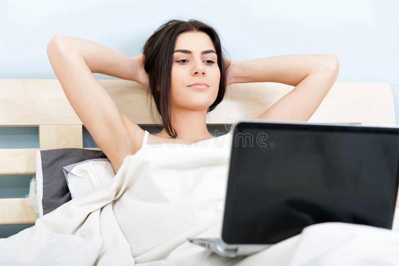 Giovane donna che si rilassa a letto con il computer portatile immagine stock libera da diritti