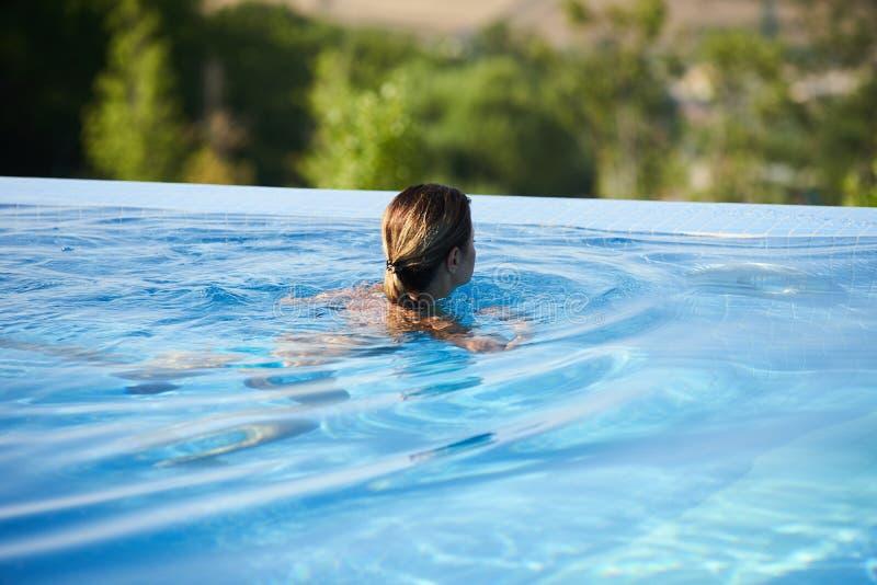 Giovane donna che si rilassa nella piscina di infinito immagini stock libere da diritti