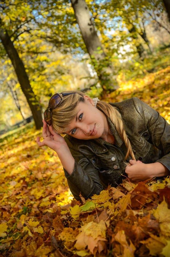 Giovane donna che si rilassa nella sosta luminosa di autunno fotografia stock