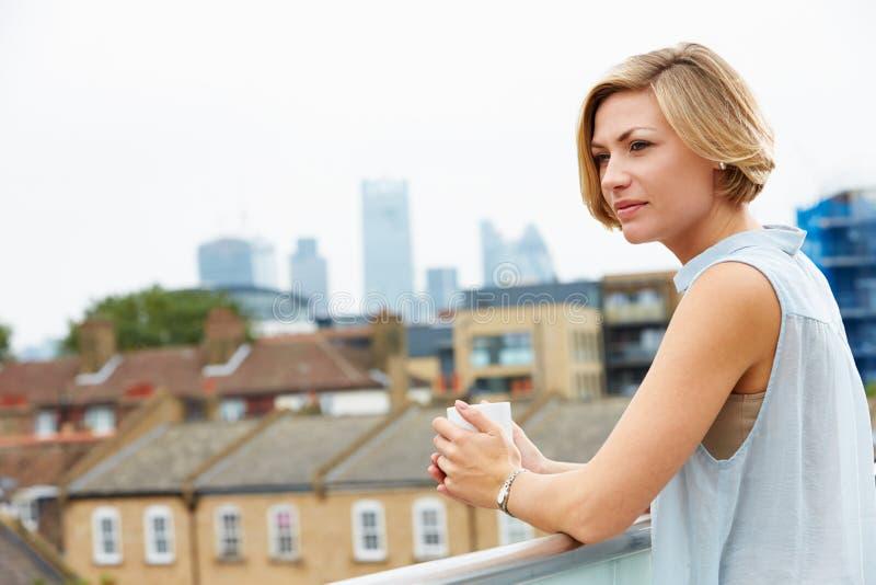 Giovane donna che si rilassa sul terrazzo del tetto con la tazza di caffè fotografia stock