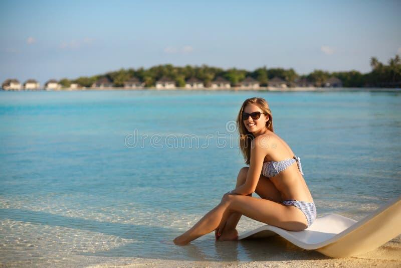 Giovane donna che si rilassa in uno sdraio moderno su una spiaggia tropicale con i vetri sopra La ragazza sta sedendosi su un let immagine stock libera da diritti
