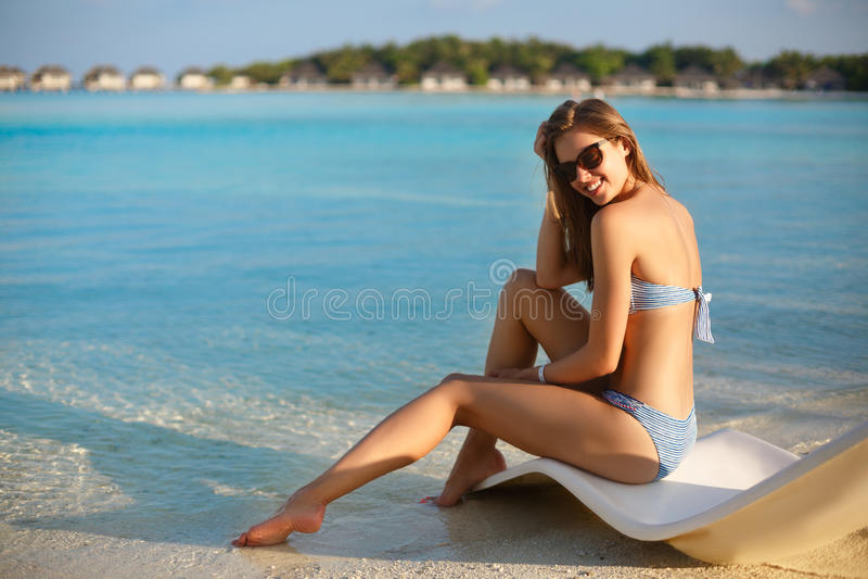 Giovane donna che si rilassa in uno sdraio moderno su una spiaggia tropicale con i vetri sopra La ragazza sta sedendosi su un let fotografia stock