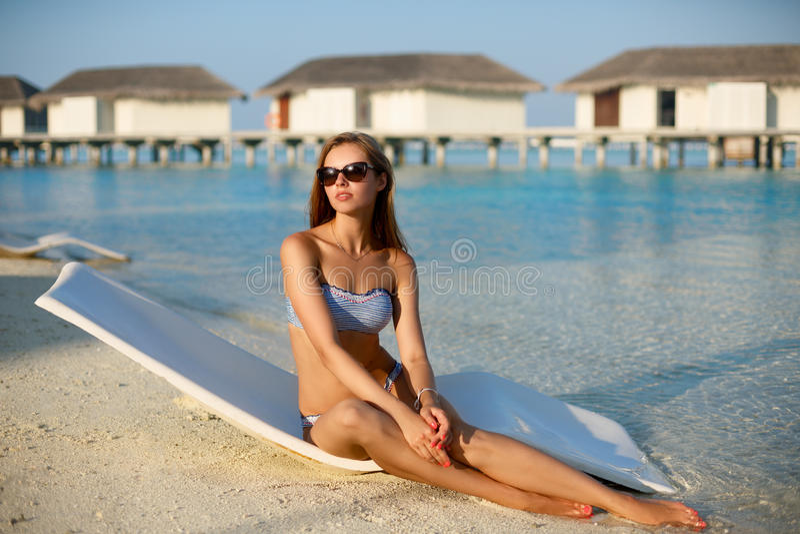 Giovane donna che si rilassa in uno sdraio moderno su una spiaggia tropicale La ragazza sta sedendosi su un letto del sole della  immagine stock libera da diritti