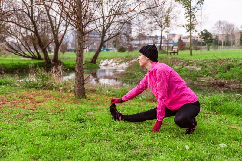 Giovane donna che si scalda e che allunga le gambe prima dell'correre su un inverno freddo, autunno del giorno dell'autunno in un immagine stock