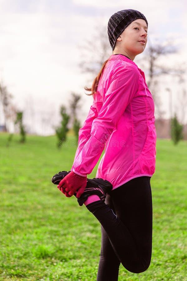 Giovane donna che si scalda e che allunga le gambe prima dell'correre su un inverno freddo, autunno del giorno dell'autunno in un fotografia stock