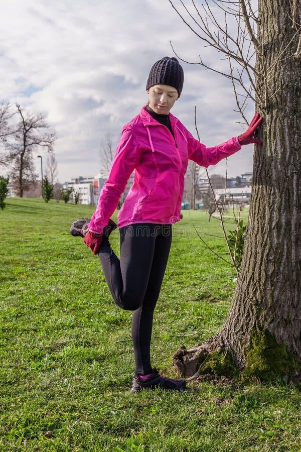 Giovane donna che si scalda e che allunga le gambe prima dell'correre immagine stock libera da diritti