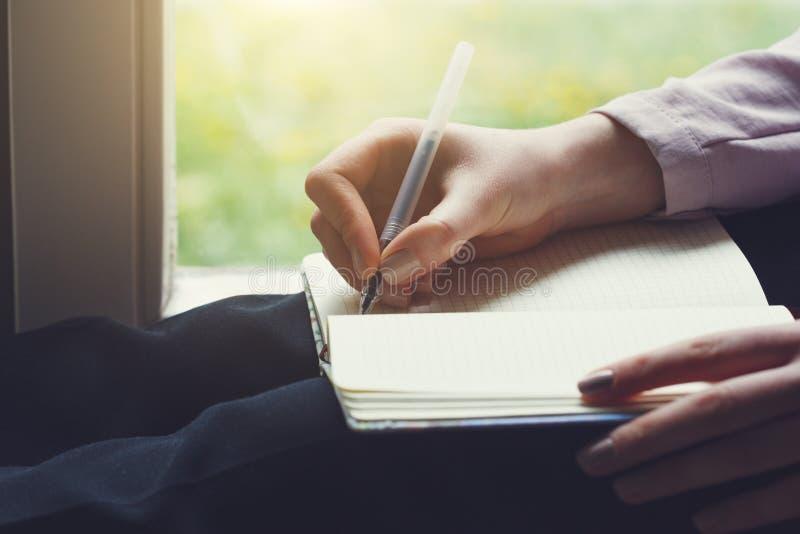 Giovane donna che si siede accanto alla finestra che scrive le note sul taccuino con la penna immagini stock