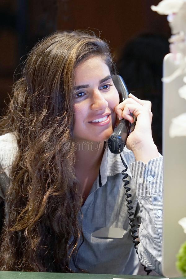 Giovane donna che si siede al suo scrittorio che funziona e che risponde ad un telefono Ca immagine stock libera da diritti