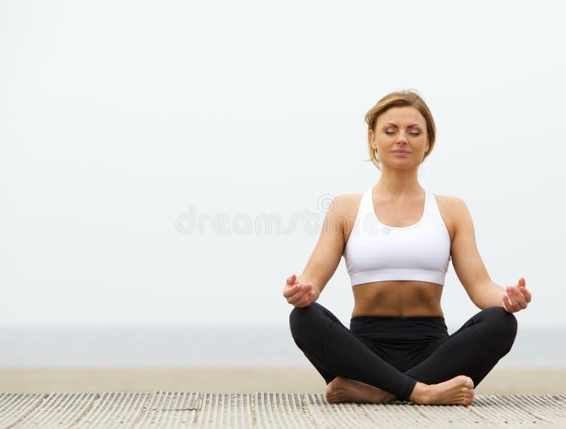Giovane donna che si siede all'aperto nella posa di yoga fotografia stock libera da diritti