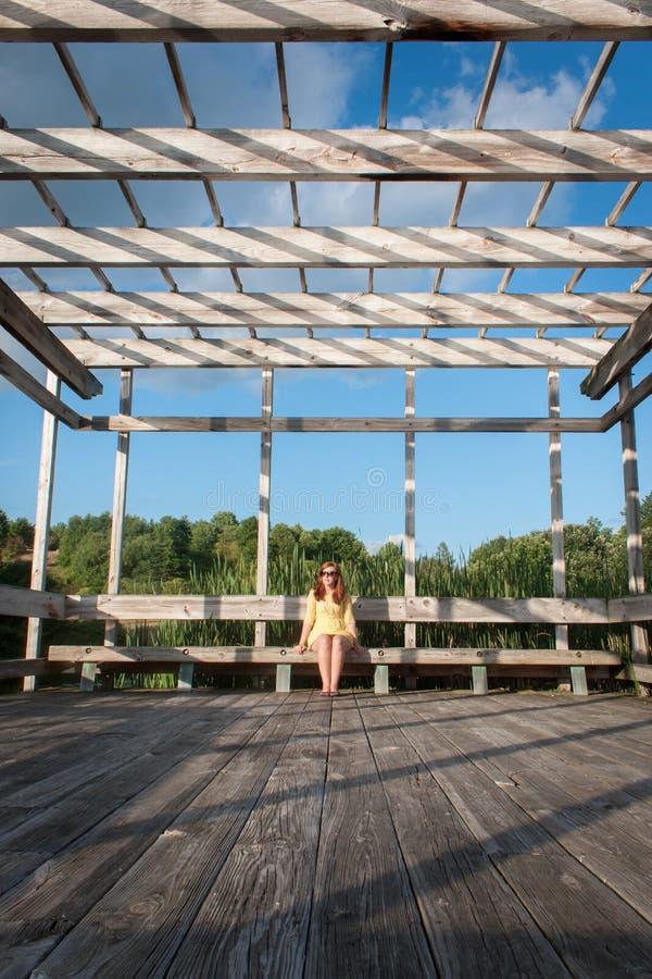 Giovane donna che si siede all'esterno fotografia stock