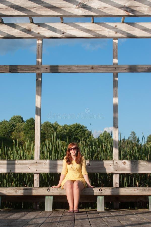 Giovane donna che si siede all'esterno immagini stock