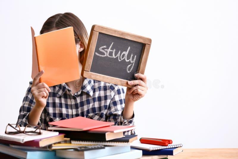 Giovane donna che si siede alla tavola con molti libri e che tiene lavagna con lo studio della parola contro il fondo bianco fotografie stock