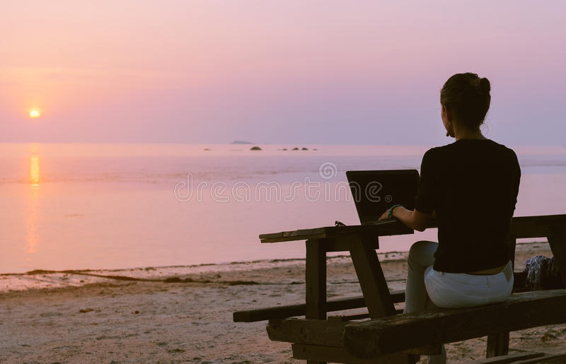Giovane donna che si siede alla tavola con un computer portatile fotografia stock libera da diritti