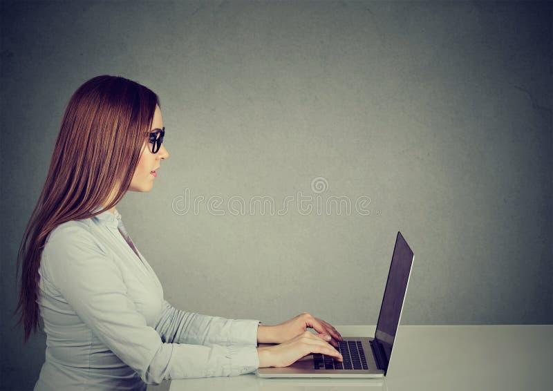 Giovane donna che si siede alla tavola facendo uso del lavorare al computer portatile fotografia stock libera da diritti