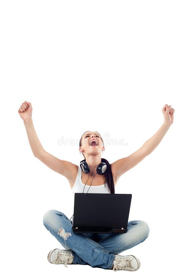 Giovane donna che si siede con il computer portatile che solleva le mani