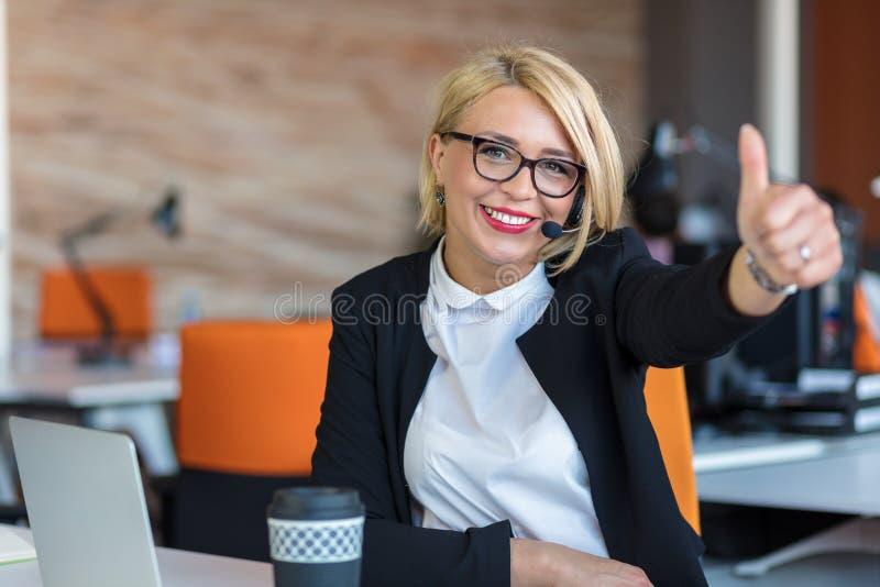 Giovane donna che si siede dietro lo scrittorio con i pollici su in un ufficio immagini stock libere da diritti